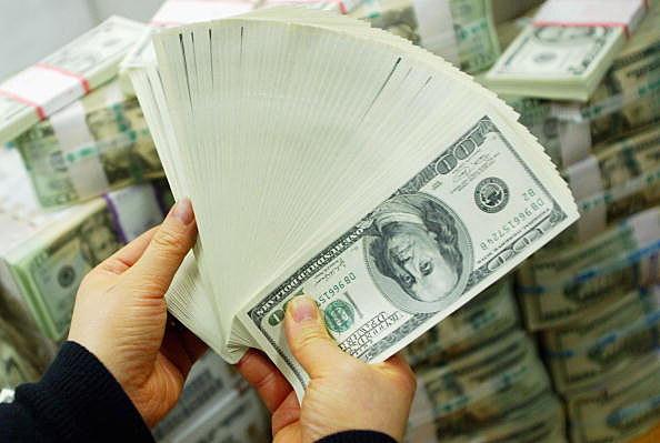 hands holding 100 dollar bills