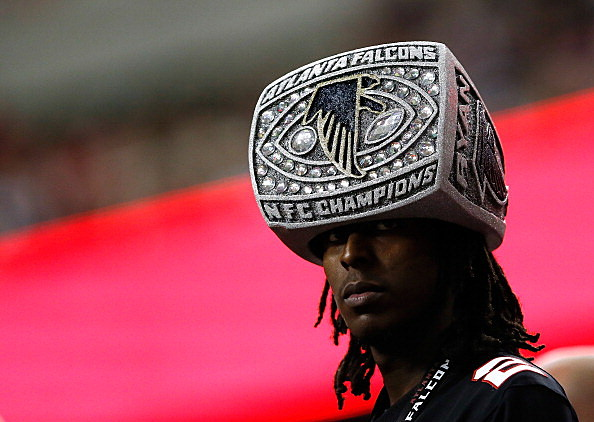 An Atlanta Falcons fan watches the game wearing a hat shaped like an NFC Championship ring
