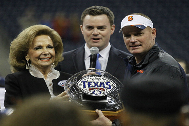 Syracuse Orange head coach Scot Schafer, right, receives the Texas Bowl championship trophy