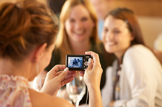 Women in restaurant holding camera with picture of female friends
